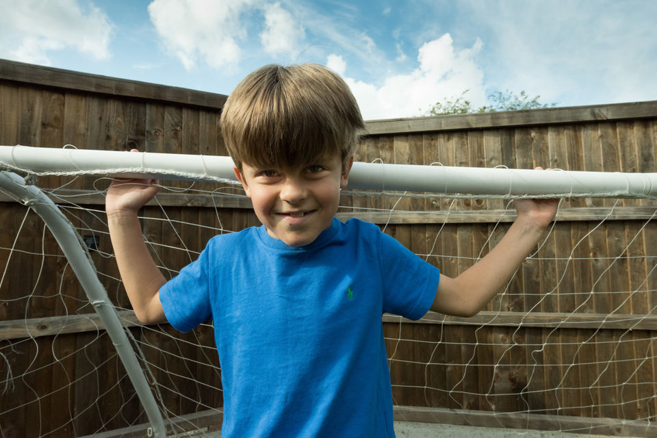 A child is smiling as he stands in a football goal