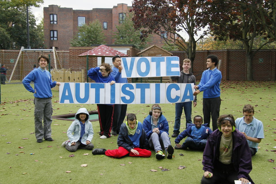Group of children with autism holding 'Vote Autistica' sign