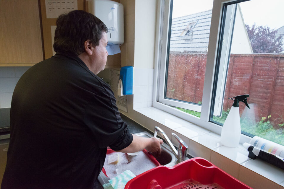 Older autistic man at the sink, looking pensively out of the window.